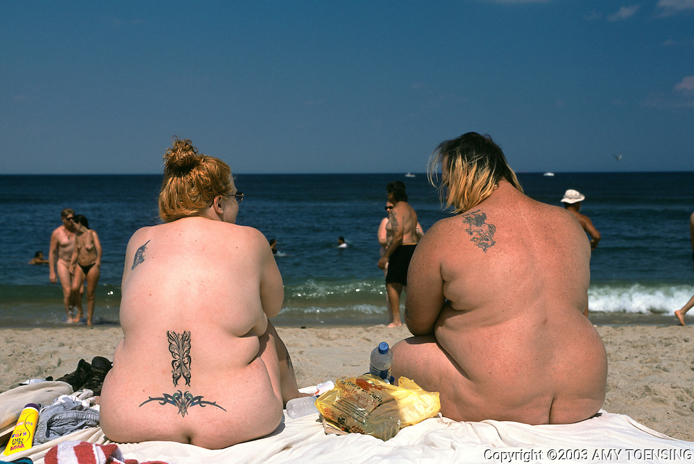 SANDY HOOK, NJ - JULY 12: A couple sits on the clothing optional area of Gunnison Beach, July 12, 2003, Sandy Hook, New Jersey. Gunnison is part of the Gateway National Recreational Area and has been a destination for nudists since the 1970s. Many of its visitors have been enjoying the sun and socializing there since its beginning. The Jersey Shore, a 127 mile stretch of coastline known for its variety of beaches, boardwalks, small towns, natural beauty and summer crowds, has been a popular summer destination for over a century. (Photo By Amy Toensing)