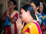 27 DECEMBER 2015 - SINGAPORE, SINGAPORE: People pray during Sunday prayers at Sri Mariamman Temple in Singapore. The Sri Mariamman Temple is Singapore's oldest Hindu temple. It is an agamic temple, built in the Dravidian style. The temple is in the downtown Chinatown district, and serves Hindu Singaporeans and Tamilians. Due to its architectural and historical significance, the temple has been gazetted a National Monument and is a major tourist attraction. The Sri Mariamman Temple was founded in 1827 by Naraina Pillai, eight years after the East India Company established a trading settlement in Singapore.       PHOTO BY JACK KURTZ