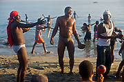 Pilgrims dance to the rhythm of drums while others cleanse themselves in the sea during a sunrise voodou ritual at Bord de Mer de Limonade, on the north coast of Haiti on July 25, 2008. After renewing their faith in the mud pit at Plaine du Nord on the days prior, pilgrims migrate to the nearby water, their faith renewed.