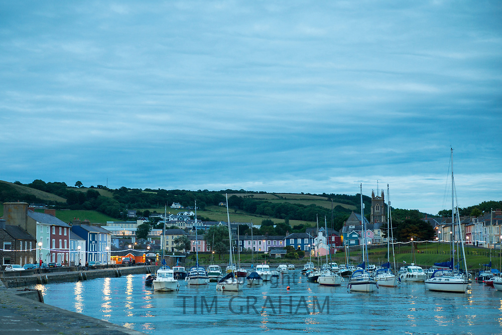 Pleasure boats - powerboats and yachts in harbour - seaside housing at sundown / dusk in Aberaeron, Pembrokeshire, Wales, UK