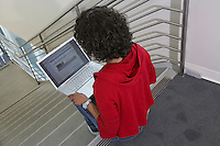 Female student using laptop on stairs