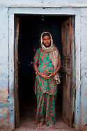 Shanno, 24, is 9 months pregnant with her 4th child as she stands for a portrait at the door of her rented house in a slum in Tonk, Rajasthan, India, on 20th June 2012. Shanno was married at the age of 17 and has had 4 successive pregnancies which affected her health and her children's health because she was unable to breastfeed them and was too poor to raise them properly. She had also given one of her sons to her sister at birth. She had also given one of her sons to her sister at birth. Her husband refuses to use contraceptives and she is not allowed to have an operation. Photo by Suzanne Lee for Save The Children UK