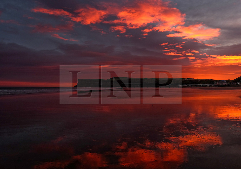 © Licensed to London News Pictures. 09/12/15<br /> Saltburn, UK. <br /> <br /> A stunning sunrise lights up the skies over the beach and cliffs at Saltburn by the Sea in North Yorkshire.<br /> <br /> Photo credit : Ian Forsyth/LNP