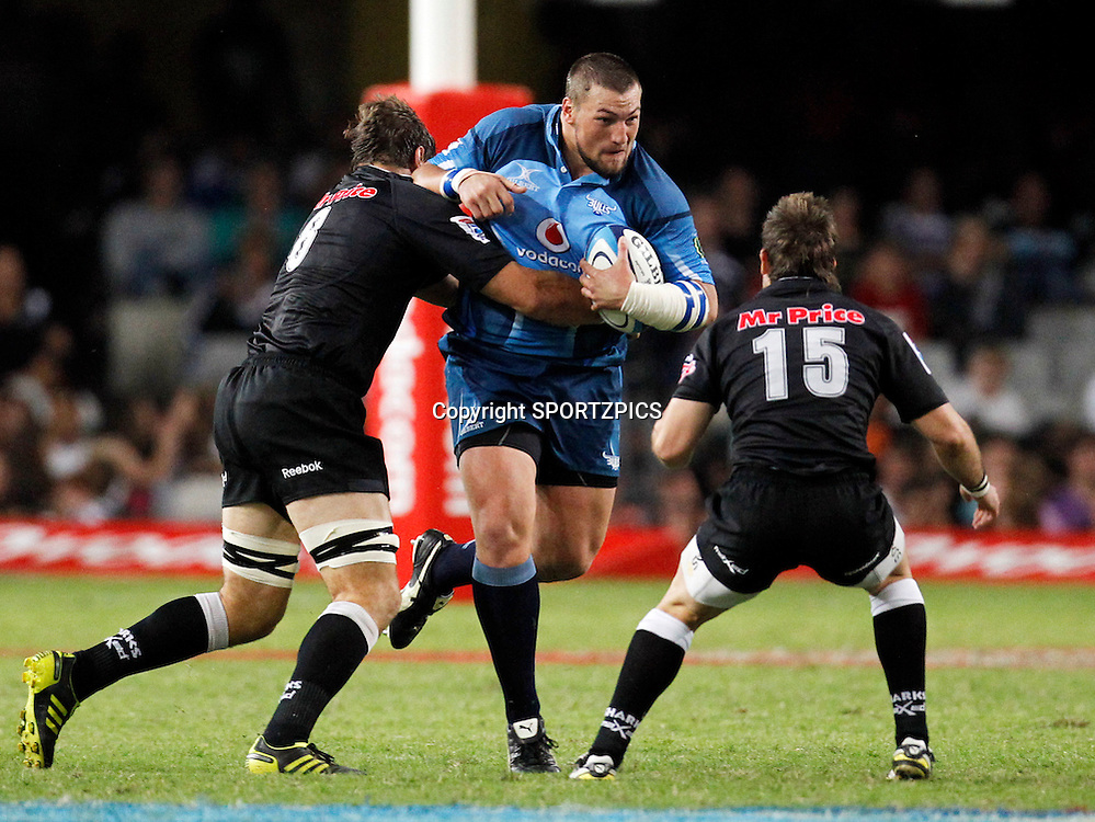 Dean Greyling is tackled by Willem Alberts and Louis Ludik during the Super 15 match between the Sharks and the Bulls played in Durban on the 21 May 2011..Photo by: SPORTZPICS