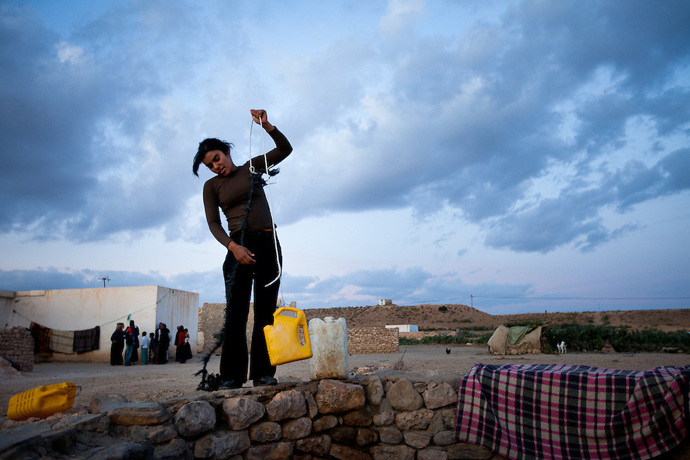 A young Berber woman hauls water outside her house in central Tunisia.