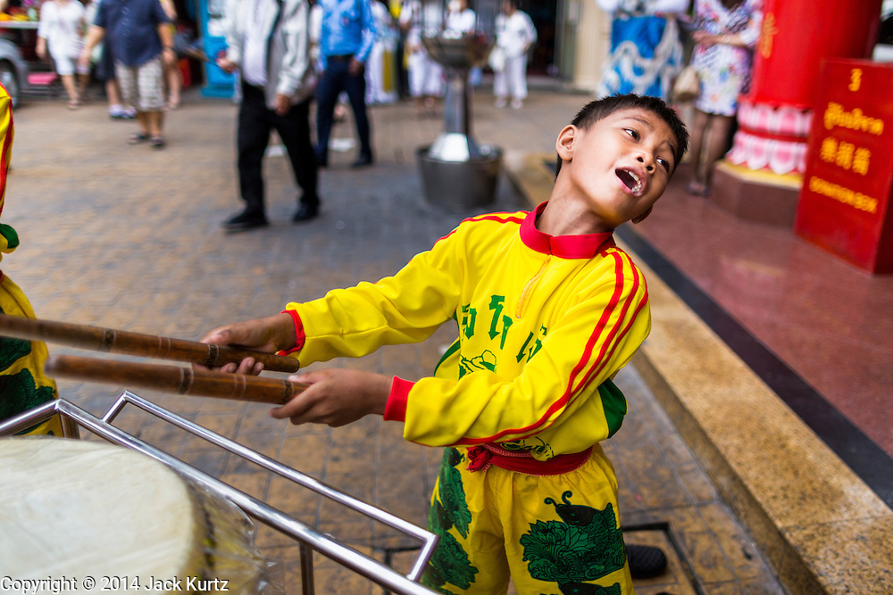 24 SEPTEMBER 2014 - BANGKOK, THAILAND:  A boy in a youth lion dance troupe plays drums in the Thian Fah Shrine in Bangkok's Chinatown. His troupe was performing on the streets of Chinatown and soliciting donations from passers by. The Vegetarian Festival is celebrated throughout Thailand. It is the Thai version of the The Nine Emperor Gods Festival, a nine-day Taoist celebration beginning on the eve of 9th lunar month of the Chinese calendar. During a period of nine days, those who are participating in the festival dress all in white and abstain from eating meat, poultry, seafood, and dairy products. Vendors and proprietors of restaurants indicate that vegetarian food is for sale by putting a yellow flag out with Thai characters for meatless written on it in red.    PHOTO BY JACK KURTZ