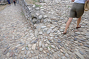 female walking up a steep cobble stoned path