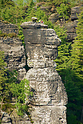 Rathen, Germany - May 23, 2010: Unidentified alpinists relax on top of one of the natural columns of the Bastei rock formations in Saxon Switzerland National Park, Germany.