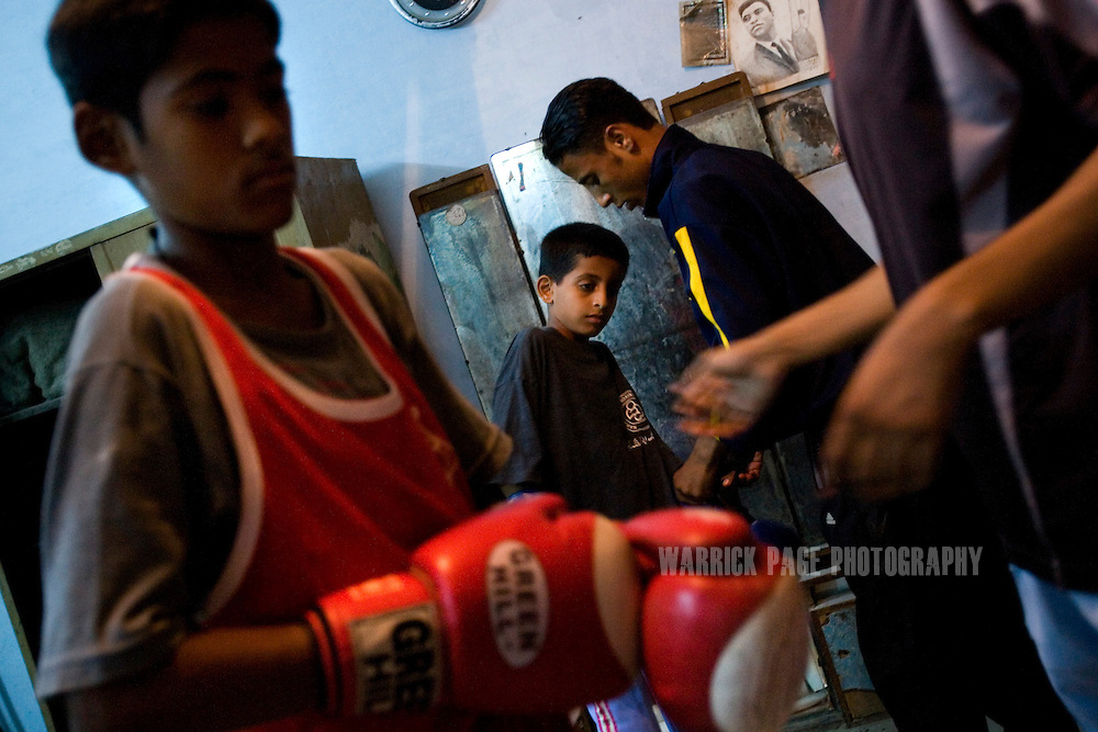 KARACHI, PAKISTAN - OCTOBER 12: Members of the Young Baloch Boxing Club prepare for training, Sunday, October 12, 2008, in Karachi, Pakistan. Lyari is Karachi's poorest, most dangerous, drug and crime-infested slum, but has produced the bulk of Pakistan's champion boxers. Boxing has been a way of survival for many of the young men, who are often sponsored by corporations and event the military, to box for them at events throughout the city and the country. Lacking in the most basic resources, including a sufficient diet, the young boxers have watched countless champions on television throughout the years, attempting to emulate their abilities. (Photo by Warrick Page)