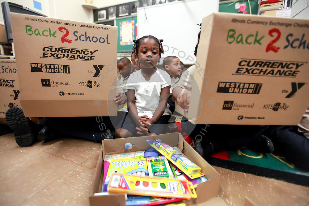 Preschool students at St. Catherine St. Lucy School in Oak Park open up boxes of school supplied given to them, Friday, Sept, 14, 2012. Each of the school's 210 students will receive a box of supplies, donated by the Illinois Currency Exchange Charitable Foundation and the Community Currency Exchange Association of Illinois, and distributed Friday by West Cook YMCA employees. | J.Geil ~ For Sun-Times Media
