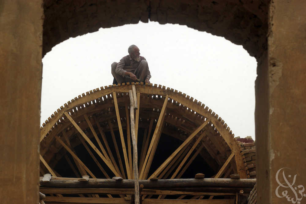 An Afghan worker constructs a section of roofing for a grain silo as part of a civil affairs project overseen by the U.S. Army 489th Civil Affairs Battalion June 8, 2002 in Kunduz, Afghanistan. The 489th has overseen a number of humanitarian projects in the area recently, including construction of a school for 4,000 Afghan girls and a Teacher's University, as part of the ongoing Operation Enduring Freedom.