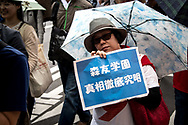 A woman holds a placard during the May Day rally in Tokyo on Monday, May 1, 2017, Thousands people participate demanding higher pays among other issues. 01/05/2017-Tokyo, JAPAN