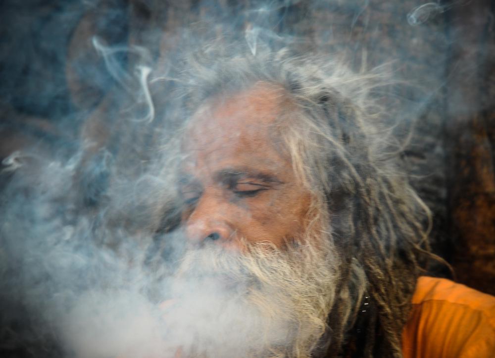 Sadhu smoking weed and blowing out smoke, Hardwar, India.