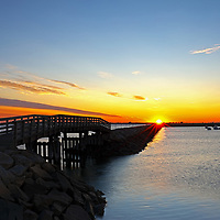 Sunrise Seaview photography of the harbor jetty with its wooden bridge at dawn in Plymouth, MA. The town of Plymouth is most famous for its historic landmarks and sites such as Plymouth Rock, the Mayflower and Plimoth Plantation. <br />