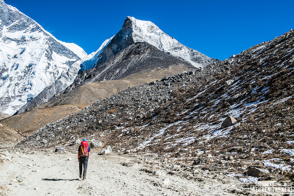 Reuben walking along the dried up river bed, towards Island Peak Base Camp, looking towards the South face of Lhotse (8414m) and Island Peak to the right.