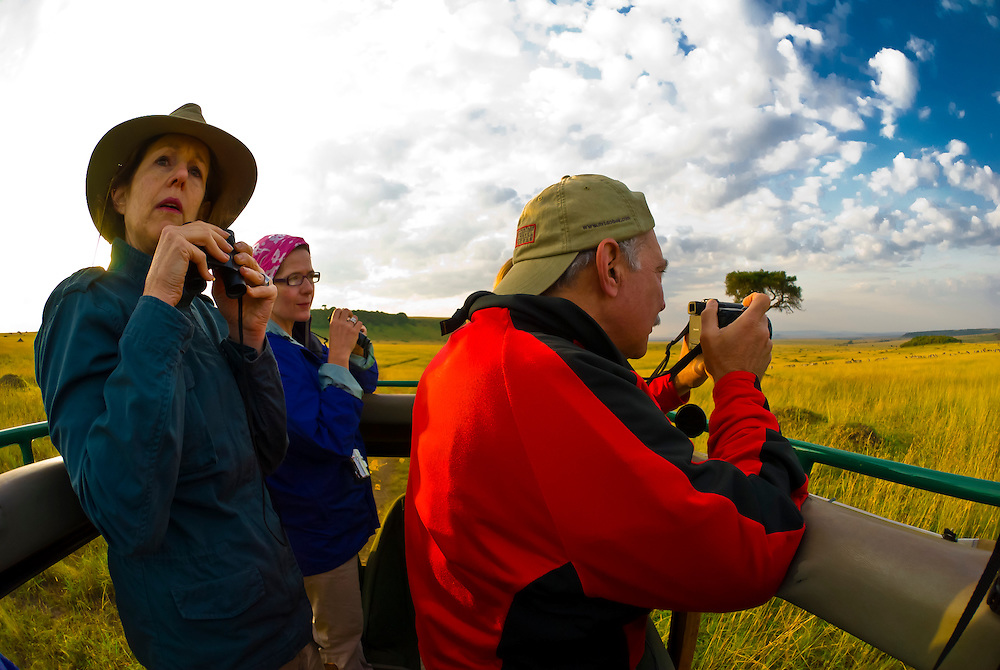 Tourists watching wildlife from the open roof of a safari vehicle, Masai Mara National Reserve, Kenya