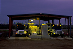 Two large transport trucks waiting under a covered structure