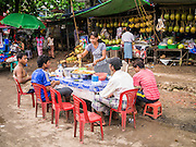 13 JUNE 2013 - YANGON, MYANMAR:   A woman serves customers at her food stall in a Yangon market. Yangon, formerly Rangoon, is Myanmar's commercial capital and used to be the national capital. The city is on the Irrawaddy River and has a vibrant riverfront.    PHOTO BY JACK KURTZ