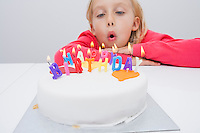 Cute girl blowing birthday candles at table in house