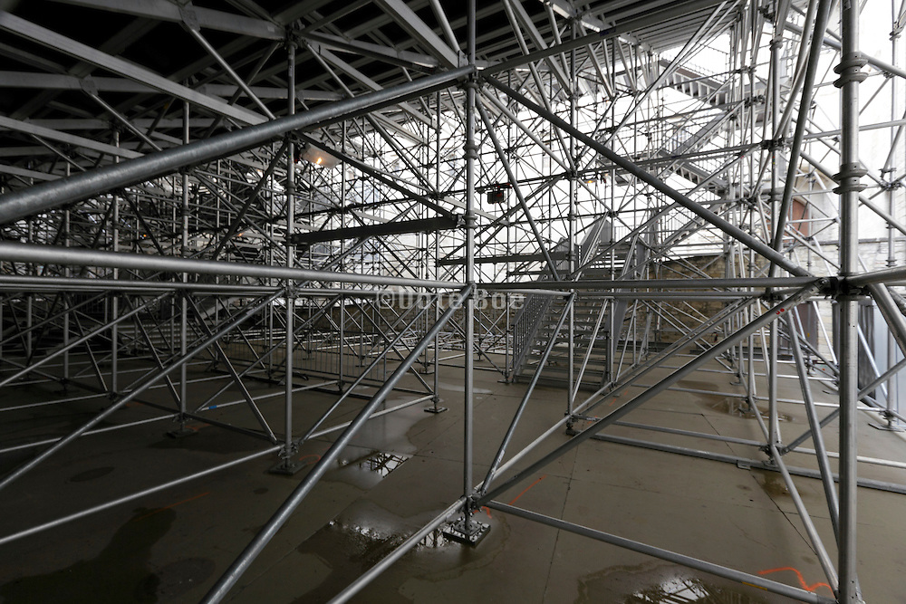 scaffolding under the public seating platform of a temporary outdoors theater event