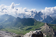 A lift from Passo Pordoi up to Sass Pordoi in the Sella Group gives a sweeping view of Dolomites peaks including their highest, glacier-clad Marmolada (3343 meters / 10,968 feet), Italy. From Pordoi Pass on state highway 48 (Grand Strader delle Dolomiti), take the rapid cable car ascent or hike up to the restaurant on Sass Pordoi at 2952m. Pordoi Pass (or Pordoijoch, 2239 meters/7346 feet) is the highest surfaced road traversing a pass in the Dolomites. On the Padon chain in the foreground (a ridge of volcanic origin carpeted with lush green pasture and wildflowers), we highly recommend hiking the Bindelweg/Viel del Pan trail starting from Pordoi Pass. The Dolomites are part of the Southern Limestone Alps, Europe. UNESCO honored the Dolomites as a natural World Heritage Site in 2009.