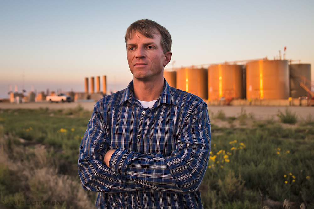 Eric Ewing next to a fracking industry site near his home in Weld County Colorado. Activity at the site proved so disruptive to his families life that they temporarily relocated to a hotel to avoid noise and fumes.