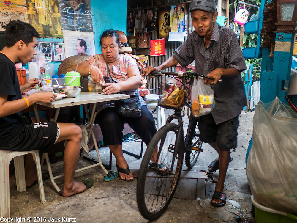 07 APRIL 2016 - BANGKOK, THAILAND: A man pushes his bike past a woman and her son eating their lunch in front of their home in the squatters' community in Mahakan Fort. Mahakan Fort was built in 1783 during the reign of Siamese King Rama I. It was one of 14 fortresses designed to protect Bangkok from foreign invaders, and only of two remaining, the others have been torn down. A community developed in the fort when people started building houses and moving into it during the reign of King Rama V (1868-1910). The land was expropriated by Bangkok city government in 1992, but the people living in the fort refused to move. In 2004 courts ruled against the residents and said the city could take the land. The final eviction notices were posted last week and the residents given until April 30 to move out. After that their homes, some of which are nearly 200 years old, will be destroyed.       PHOTO BY JACK KURTZ