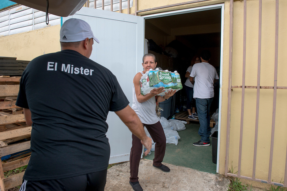 Toa Baja, PR, November 10, 2017--Eric Rossner and Nilma Torres Rivera load water into their cars before driving supplies to neighborhoods still without power and water 50 days after Hurricane Maria.  They are teachers and staff of Escuela Delia Cabán in Tao Baja, PR and their school has served as a distribution point for the Puerto Rico Recovery Fund's emergency relief efforts since it was established days after the storm hit September 20, 2017.  Photo by Lori Waselchuk/BRAF