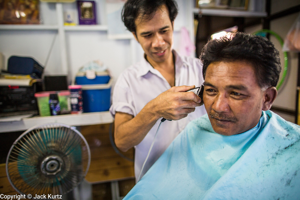 13 JANUARY 2013 - BANGKOK, THAILAND: A barber cuts a man's hair in his barbershop in the Bang Luang neighborhood of Bangkok. The Bang Luang neighborhood lines Khlong (Canal) Bang Luang in the Thonburi section of Bangkok on the west side of Chao Phraya River. It was established in the late 18th Century by King Taksin the Great after the Burmese sacked the Siamese capital of Ayutthaya. The neighborhood, like most of Thonburi, is relatively undeveloped and still criss crossed by the canals which once made Bangkok famous. It's now a popular day trip from central Bangkok and offers a glimpse into what the city used to be like.     PHOTO BY JACK KURTZ