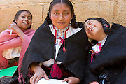 "26 APRIL 2005 - SAN CRISTOBAL DE LAS CASAS, CHIAPAS, MEXICO:Girls read the bible in Mayan before a Catholic mass in the Chumalan Indian community of Bautista Chico near San Cristobal de las Casas, Chiapas, Mexico. The Catholic Church in the Chiapas highlands is facing a threat from evangelical Protestant churches, which are experiencing explosive growth, and from ""traditionalist"" Catholic churches, which are not affiliated with the San Cristobal diocese and are controlled by local politicians and powerful indigenous leaders affiliated with the politicians. The traditionalists burn down churches and chapels affiliated with the diocese, threaten the priests and put indigenous men who worship with the diocese in jail.  PHOTO BY JACK KURTZ"
