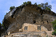 Looking up at part of the National Museum of Prehistory with a statue of Cro-Magnon Man on the cliff side balcony in the tiny village of Les Eyzies-de-Tayac in the Dordgne region of Perigord, France.