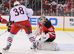 Feb 27, 2014; Newark, NJ, USA; New Jersey Devils goalie Cory Schneider (35) makes a save while Columbus Blue Jackets center Boone Jenner (38) looks for the loose puck during the second period at Prudential Center.
