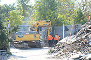 Workers stand by as heavy machinery is moved in during demolition of the buildings at the Bristol Rd. and Butler Pike intersection Thursday October 8, 2015 in Chalfont, Pennsylvania. (Photo by William Thomas Cain)