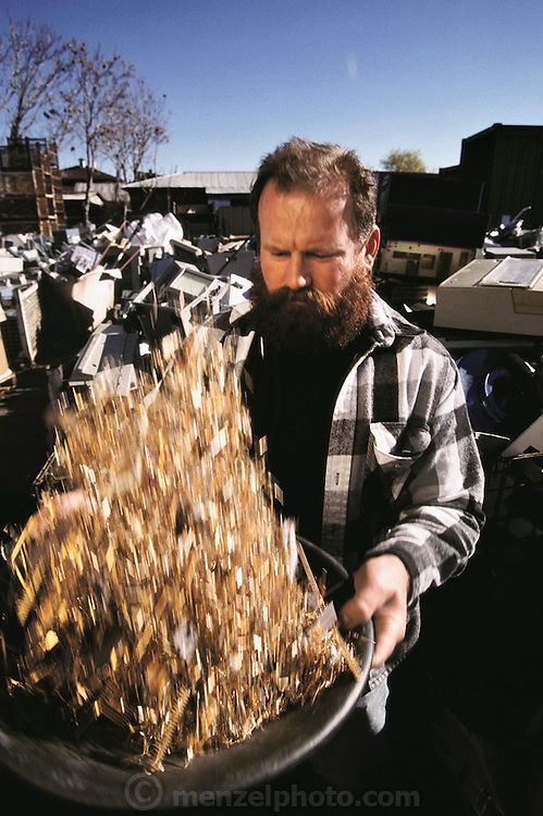 "Silicon Valley, California; Essential Elements computer recycling yard in San Jose. Owner and founder Bob Kaiser, seen here with a pan of gold plated parts recovered from computers, was a roofing contractor who panned for gold in California rivers on weekends until a friend told him ""there's gold in computers"". He started by scavenging dumpsters and now runs a multi-million dollar business recycling computers for precious metals and for scrap sales to mainland China. (1999)."