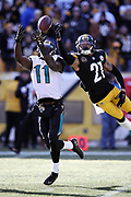 Jacksonville Jaguars wide receiver Marqise Lee (11) tries to catch a deep pass that gets tipped and broken up in the second quarter by leaping Pittsburgh Steelers cornerback Joe Haden (21) during the NFL 2018 AFC Divisional playoff football game against the Pittsburgh Steelers, Sunday, Jan. 14, 2018 in Pittsburgh. The Jaguars won the game 45-42. (©Paul Anthony Spinelli)