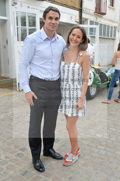 ADAM BIDWELL and LAVINIA BRENNAN at the launch of Dundas London held at Fiskins Classic Car Showroom, 14 Queens Gate Place Mews, London on 25th June 2014.