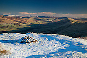 A snow-capped Lord's Seat on Rushup Edge looks over the Vale of Edale. Peak District.