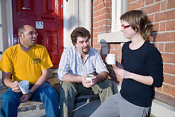 Residents of Igloo; an independent backpackers hostel in Nottingham; sitting on the steps chatting to a staff member,