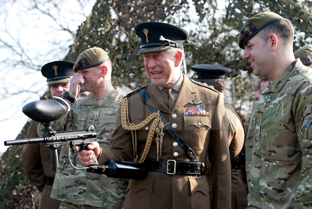 © Licensed to London News Pictures. 01/03/2012. Hounslow, UK.  HRH  Prince Charles, The Prince of Wales being given a demonstration in how to fire a paintball gun by Guardsman Robert Davies (right) of The Prince of Wales Guards after Presenting leeks to 1st Battalion The Welsh Guards at Cavalry Barracks,  Hounslow, London on St David's Day, March 1st, 2012.  Two-thirds of the Battalion's 600 soldiers are due to be deployed to Afghanistan in the next two weeks. Photo credit : Ben Cawthra/LNP