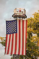 Garden City, New York, U.S. - June 6, 2014 - A large American Flag was suspended from a cherry picker high over the intersection of Franklin Avenue and 7th Street, during the Garden City Belmont Stakes Festival, celebrating the 146th running of Belmont Stakes at nearby Elmont the next day. There was street festival family fun with live bands, food, pony rides and more, and a main sponsor of this Long Island night event was The New York Racing Association Inc.
