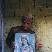 "A young inhabitant of the poor neighborhood ""Canal de Arruda""  with a portrait of Santa Barbara, the result of religious syncretism. Santa Barbara is the equivalent of the Yoruba deity Iemanjá, queen of the waters."