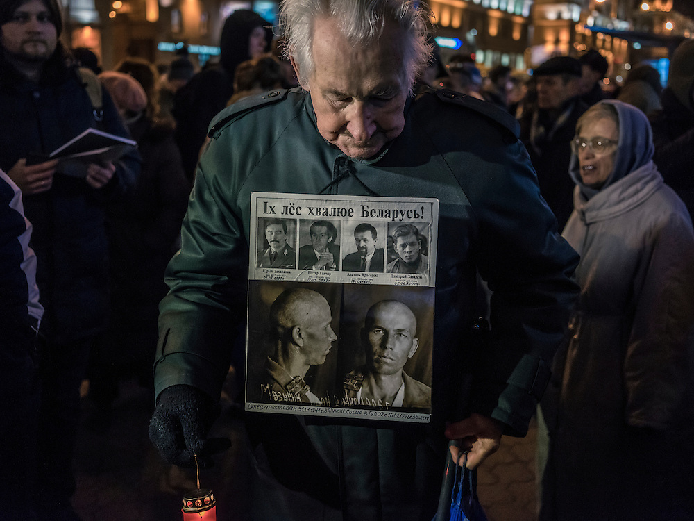 A man wears a sign commemorating his father's death in the Soviet gulag system as well as four men who went missing in 1999 at the start of a rally organized by Mikalai Statkevich, a former opposition presidential candidate and political dissident, to commemorate the nineteenth anniversary of a referendum which enshrined authoritarian changes in Belarus's constitution on Tuesday, November 24, 2015 in Minsk, Belarus.