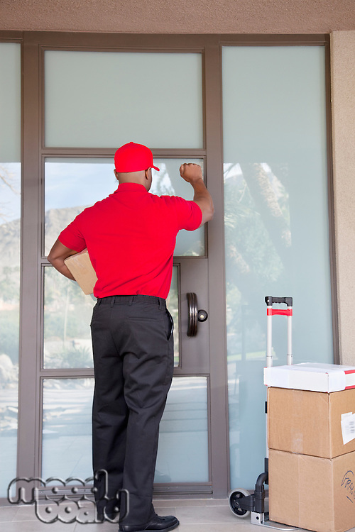Rear view of a delivery man knocking on door