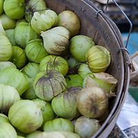 Tomatillos in a bushel basket at a farmers market.