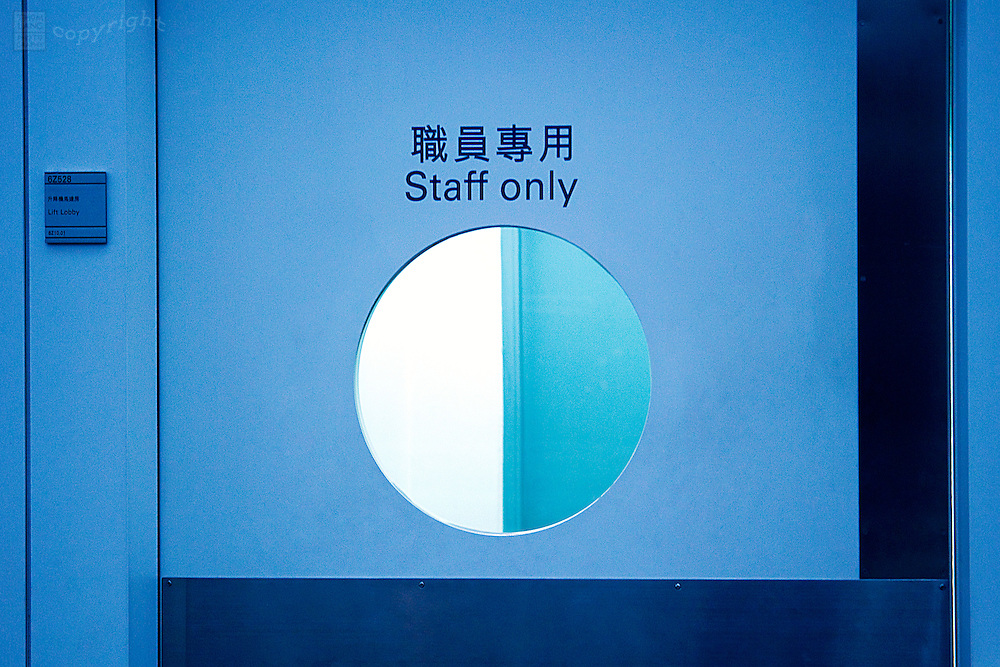 "A sign reads: ""Staff Only"" in English & also Chinese characters on a door with a round window in the Hong Kong Airport."