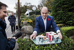 © Licensed to London News Pictures. 09/11/2017. Whitam, UK. Alex Sawyer (R), husband of Priti Patel, brings out a tray of tea and cake for reporters waiting outside their house. Priti Patel resigned from government yesterday. Photo credit: Peter Macdiarmid/LNP