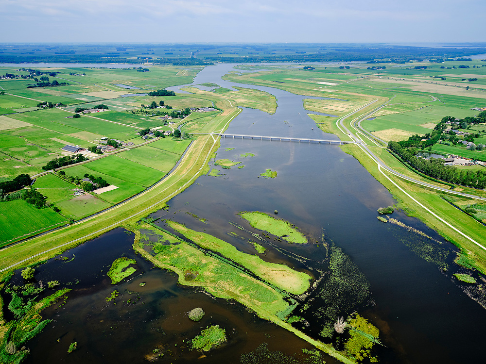 """Nederland, Overijssel, Gemeente Kampen; 21–06-2020; het Reevediep richting monding in het Revemeer (voorheen Drontermeer). In het midden  de Nieuwendijkbrug, met deel van De Enk in de voorgrond, Flevoland aan de horizon.<br /> Het Reevediep is aangelegd in het kader van het project Ruimte voor de Rivier om bij hoogwater water af te voeren voordat dit het nabij gelegen Kampen bereikt, direct naar het IJsselmeer, de 'bypass Kampen'. Het Reevediepgebied is ook een natuurgebied en vormt een ecologische verbindingszone tussen rivier de IJssel en Drontermeer.<br /> Reevediep towards the mouth in the Revemeer (formerly Drontermeer). The Nieuwendijkbrug, Flevoland on the horizon.<br /> The Reevediep has been constructed as part of the Room for the River project, and functions to discharge high waters before reaching the nearby Kampen, directly to the IJsselmeer, the """"bypass Kampen"""". The Reevediep area is also a nature reserve and forms an ecological connecting zone between the river IJssel and Drontermeer.<br /> <br /> luchtfoto (toeslag op standard tarieven);<br /> aerial photo (additional fee required)<br /> copyright © 2020 foto/photo Siebe Swart"""