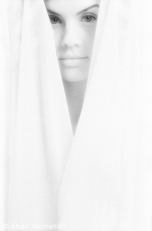White cloth framing face and eyes of woman