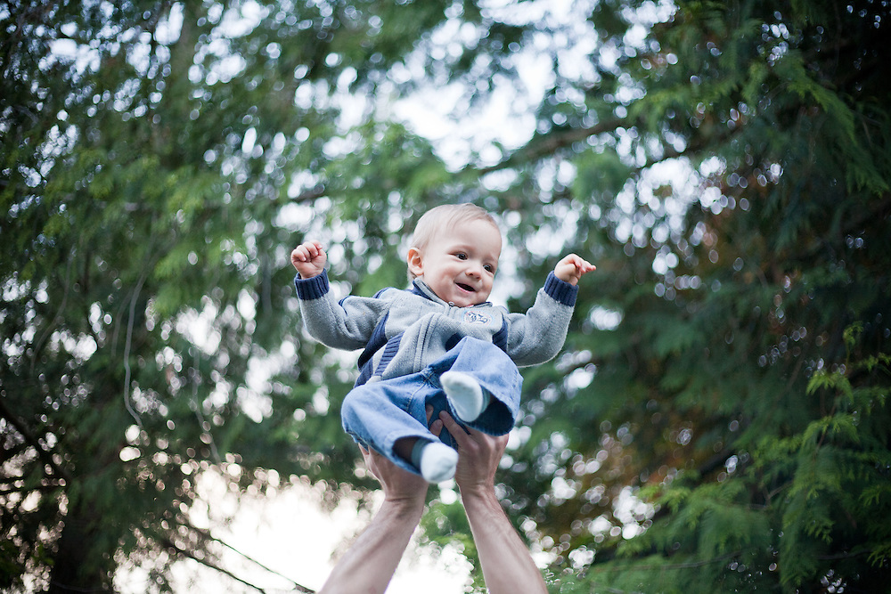Portraits of a baby boy being held up in the air with a background of trees and countryside.