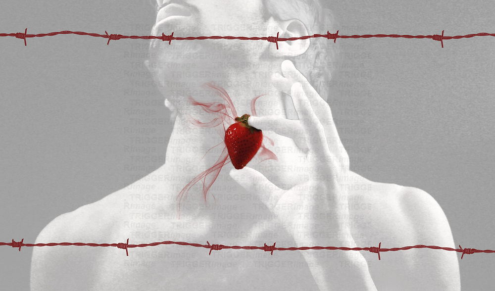A young man holding a strawberry between two lengths of barbed wire